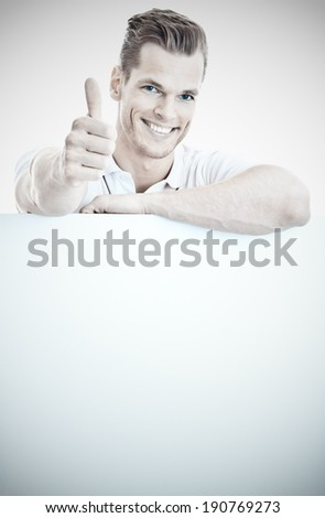 Young man standing behind a whiteboard and showing thumb up - much space for own text - stock photo