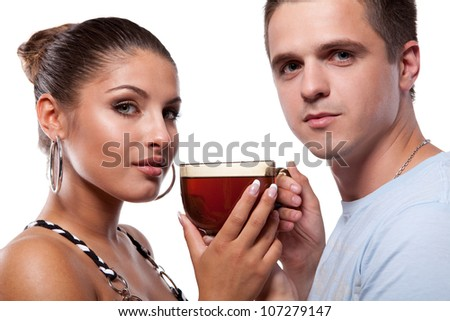 Young man standing beside beautiful woman and they holding a large cup of tea - stock photo