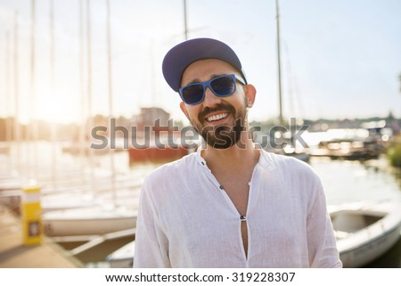 Young man standing in yacht port on sunset and smiling - stock photo