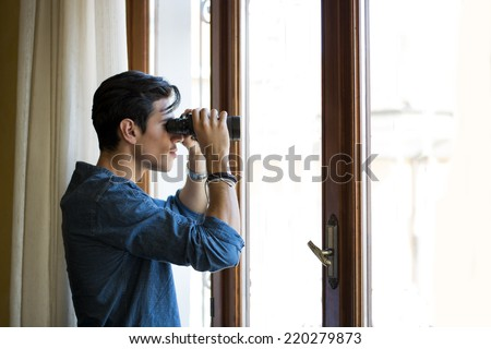 Young man standing looking through a glass door with binoculars as he watches something in the distance - stock photo