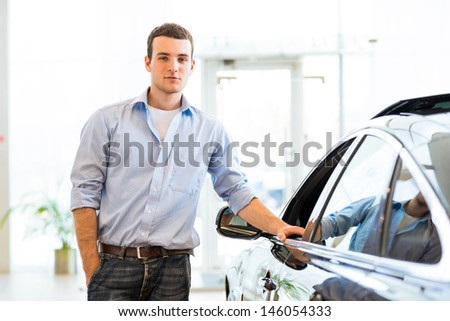 young man standing near a car in a showroom, put his hand on the car door - stock photo