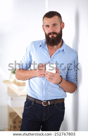 Young man  standing near wall and holding cup of coffee - stock photo