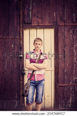 young man standing next to a wooden wall outdoors - stock photo