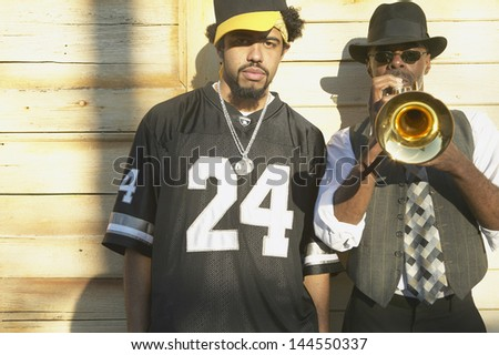 Young man standing next to senior man playing trumpet - stock photo