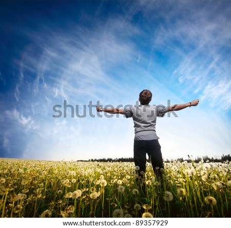 Young man standing on a meadow with raised hands - stock photo