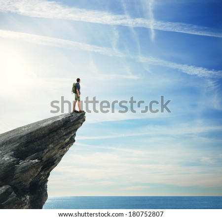 Young man standing on a peak - stock photo