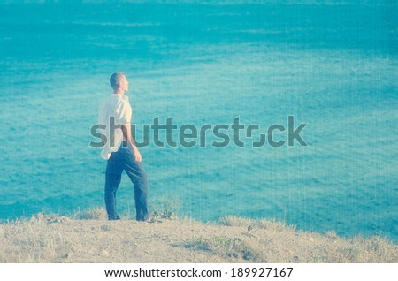 Young man standing on a rock and looking at sea. Filtered image: vintage, grunge and texture effects - stock photo