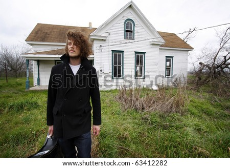 Young man standing on front of an abandoned house, holding a guitar case. - stock photo