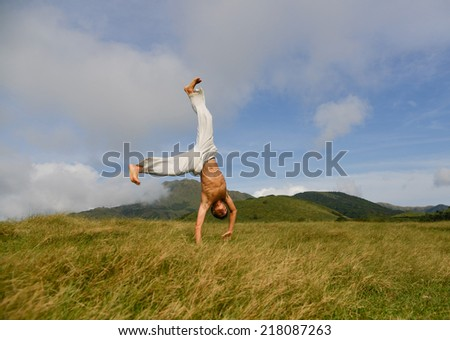 young man standing on his hands taken on mountain with a cloudy sky - stock photo