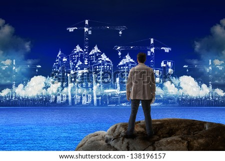 young man standing on rock and looking to building construction use for construction industries business - stock photo