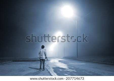young man standing on the road in the fog near the forest. blue toning - stock photo