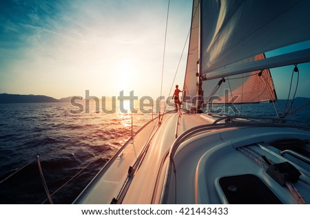 Young man standing on the yacht in the sea at sunset - stock photo