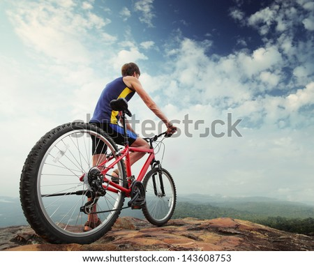 Young man standing with bicycle on top of a mountain - stock photo