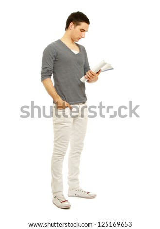 Young man standing with book, isolated on white background - stock photo