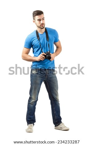 Young man standing with digital camera around neck. Full body length portrait isolated over white background. - stock photo