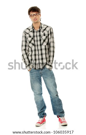 Young man standing with hands in pockets, wearing black glasses, plaid jeans and red sneakers. Isolated on the white background. - stock photo