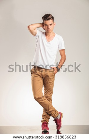 young man standing with legs crossed on beige studio background - stock photo