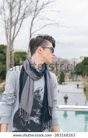 young man stands on a city street with sunglasses - stock photo