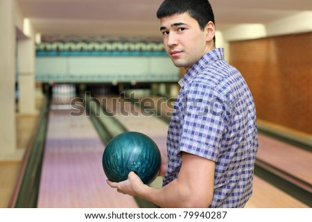Young man stands sideways and and holds  ball for bowling - stock photo
