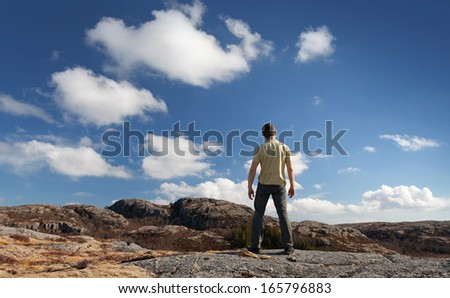 Young man staring at blue sky stands on rocky ground - stock photo
