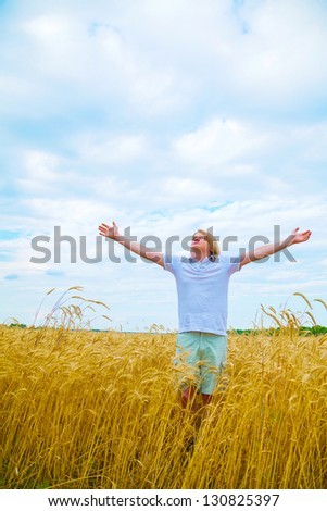 Young man staying with raised hands at sunset time - stock photo