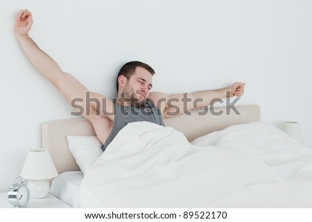Young man stretching his arms in his bedroom - stock photo