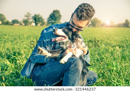 Young man stroking his playful dog - Cool dog and young man having fun in a park - Concepts of friendship,pets,togetherness - stock photo