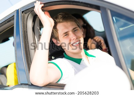 young man stuck his hand out of the window of the car, country car trip - stock photo