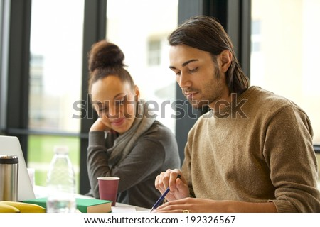 Young man studying hard with woman sitting by. University students preparing for final exams. - stock photo