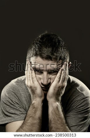 young man suffering depression, headache , migraine , mental  breakdown and pain on studio black background covering face with hands in crisis and stress - stock photo