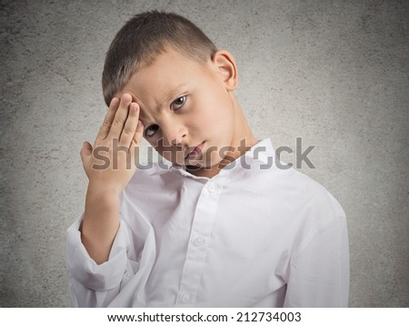 Young man suffering from headache. Closeup portrait little boy having a head ache, isolated grey wall background. Negative human face expressions, emotions, feelings, body language, life perception - stock photo