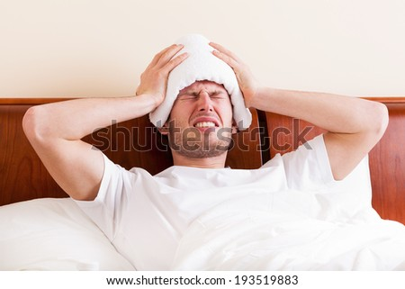 Young man suffering from headache lying in bed - stock photo
