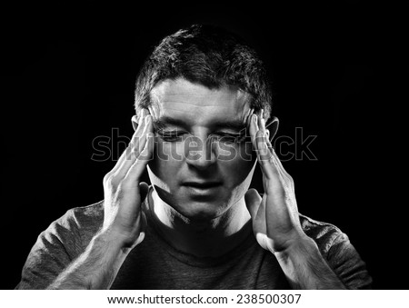 young man suffering migraine and headache in intense pain feeling desperate and sick with hands on tempo isolated on studio background black and white - stock photo