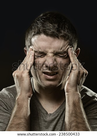 young man suffering migraine and headache in intense pain feeling desperate and sick with hands on tempo isolated on black studio background - stock photo