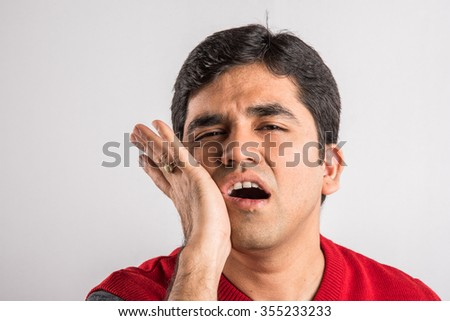 Young man suffers from tooth ache, indian man and tooth ache, asian man and tooth ache,  Portrait of young man with toothache, Unhappy asian man having a toothache - stock photo