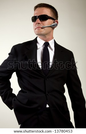 Young man suggesting a secret service agent or secret policeman appears to be reaching for a weapon. - stock photo