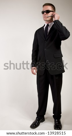 Young man suggesting a secret service agent or secret  policeman listening on a headset. - stock photo
