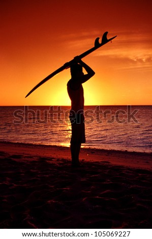 Young man surfer carrying surfboard during sunrise - stock photo
