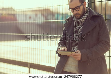 Young man surfing the internet on a tablet outdoor - stock photo
