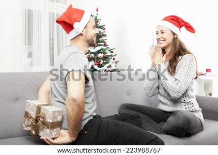 young man surprise girlfriend with gift for christmas with present box behind his back  - stock photo