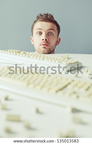 Young man surprised and peeping out from table with keyboards - stock photo