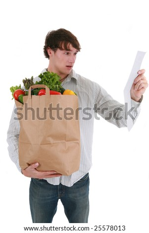 Young Man Surprised Expression Looking at Groceries Store Receipt - stock photo