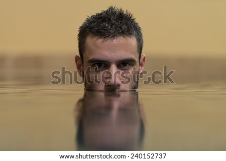 Young Man Swimming In Pool With Face Half Submerged Looking At Camera - stock photo