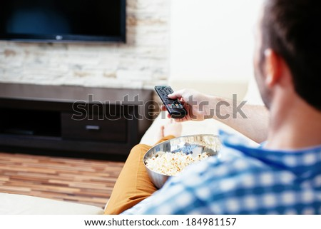 Young man switching on a tv set with a remote control - stock photo