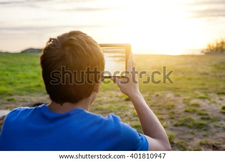 Young Man Take a Photo of Sunset with Tablet Computer - stock photo