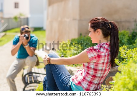 Young man take photo of his girlfriend sitting park bench - stock photo