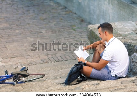 Young man taking a break on the stairs in the old town, reading a book while his bicycle is beside him - stock photo