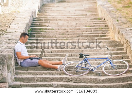 Young man taking a break on the stairs in the old town, using laptop while his bicycle is beside him - stock photo