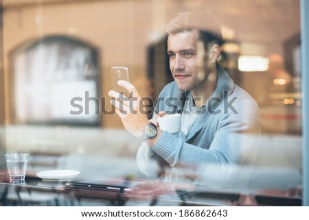 Young man taking a selfie in coffee shop - stock photo