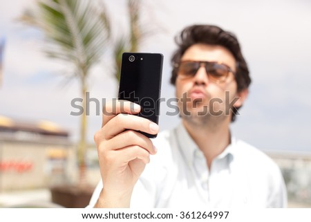 Young man taking a selfie with his mobile phone - stock photo